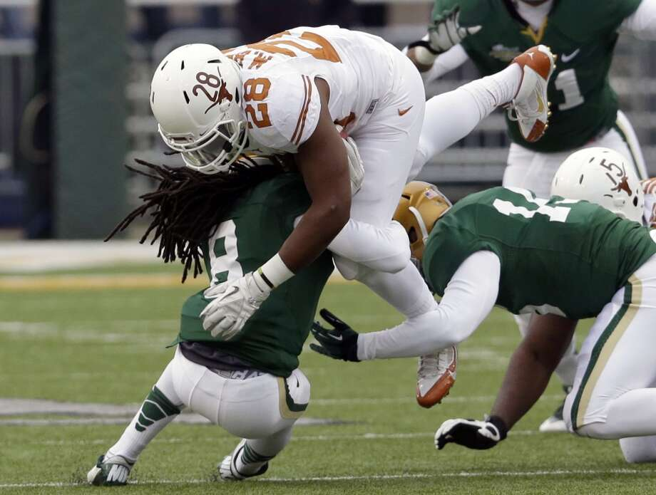 Texas running back Malcolm Brown (28) is stopped by Baylor's K.J. Morton (8) and Brody Trahan (15). Photo: LM Otero, Associated Press