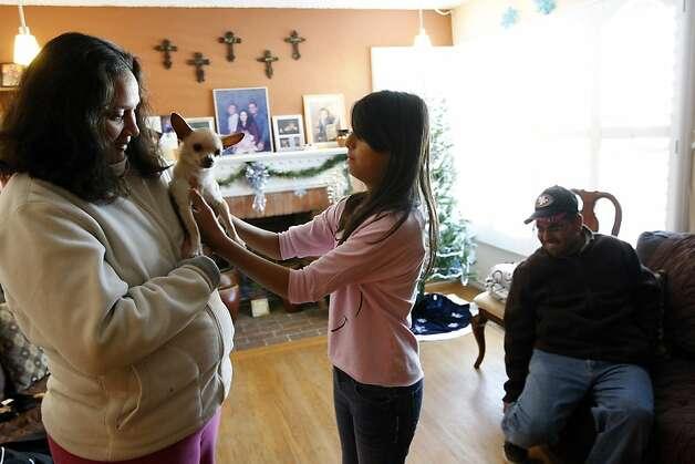 Patti Castillo, Kayla Castillo, reaching for the family dog, Chico, and Robert Castillo live in Richmond. Photo: Michael Short, The Chronicle