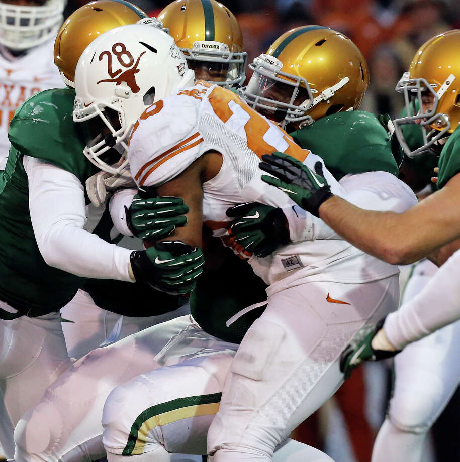 Texas Longhorns running back Malcolm Brown is tackled by Baylor Bears defenders during second half action Saturday Dec. 7, 2013 at Floyd Casey Stadium in Waco, Tx. Baylor won 30-10. Photo: Edward A. Ornelas, San Antonio Express-News / © 2013 San Antonio Express-News