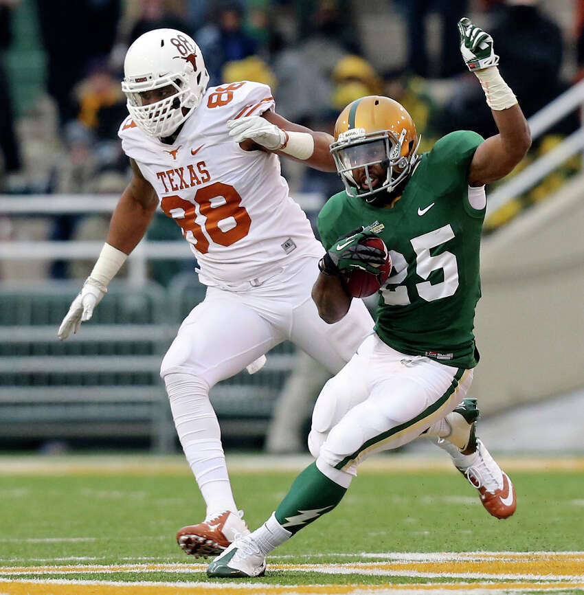 Baylor Bears running back Lache Seastrunk heads up field around Texas Longhorns defensive end Cedric Reed during first half action Saturday Dec. 7, 2013 at Floyd Casey Stadium in Waco, Tx.