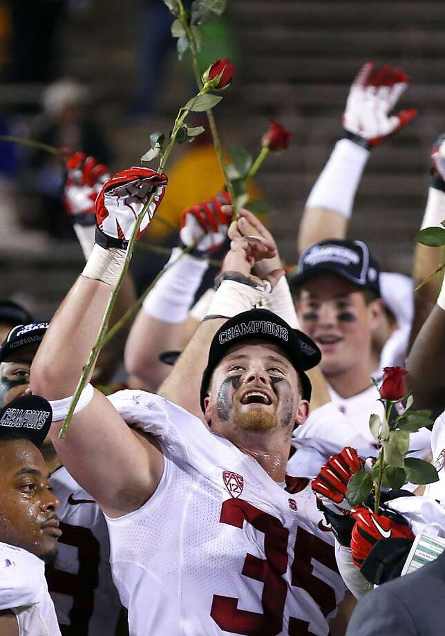 Stanford's Jarek Lancaster (35) celebrates with teammates after the NCAA Pac-12 Championship football game win against Arizona State Saturday, Dec. 7, 2013, in Tempe, Ariz.  Stanford defeated Arizona State 38-14.  The players hold up roses as the are headed to the Rose Bowl. (AP Photo/Ross D. Franklin) Photo: Ross D. Franklin, Associated Press