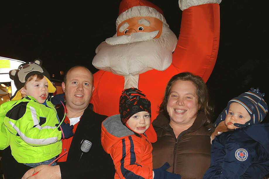Angelus and Wendy Papageorge, with their children Jack, 3; Ryan, 2, and Tyler, 8 months, at their home at 2011 Kings Highway East, where they hosted a hosted a celebratory gathering Saturday for the lighting of their extravagant Christmas decorations and collected donations for charity. Photo: Mike Lauterborn / Fairfield Citizen contributed