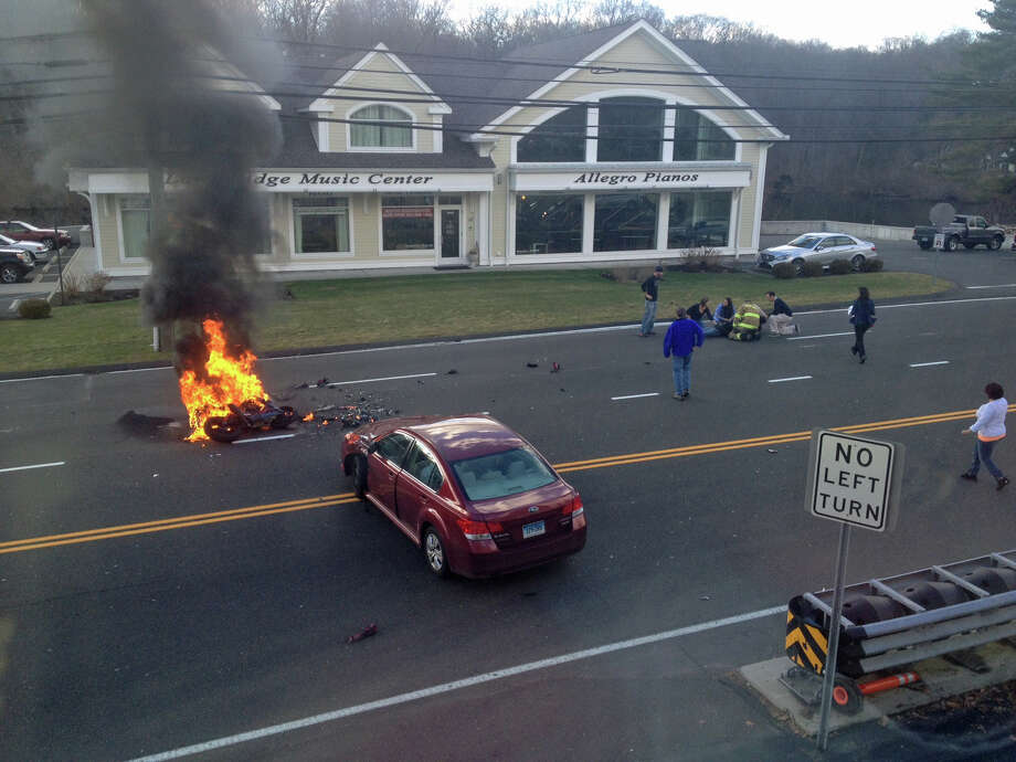 Stamford police investigate an accident involving a car and a motorcycle on Long Ridge Road near the Merritt Parkway on Saturday afternoon. The motorcycle burst into flames after the impact. Photo: Contributed Photo / Stamford Advocate Contributed