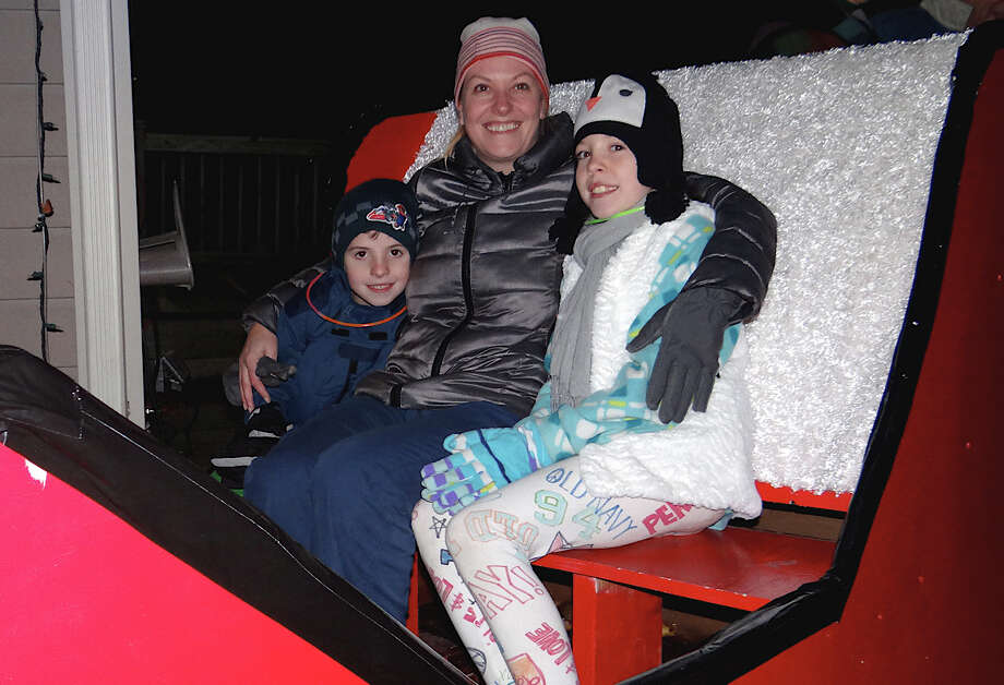 Kate Golding of Fairfield and her children Jake, 6, and Ava, 9, in a sleigh at the Papageorge family's house lighting Saturday at 2011 Kings Highway East. Photo: Mike Lauterborn / Fairfield Citizen contributed