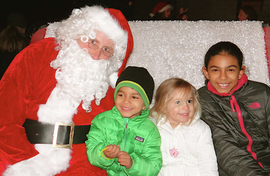Santa with young fans at the Papageorge home on Saturday, from left, Omar Osman, 3; Ella Kensek, 3, and Kinzey Osman, 9. Photo: Mike Lauterborn / Fairfield Citizen contributed