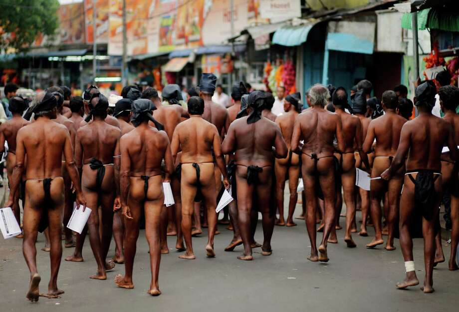 Sri Lankan farmers walk on a street during a protest in Colombo, Sri Lanka, Monday, Dec. 2, 2013. The farmers distributed leaflets and took to the streets wearing loincloths to create awareness about the issues faced by them and to protest against the government's failure to provide solutions to their long standing grievances. Photo: Eranga Jayawardena, AP / AP2013