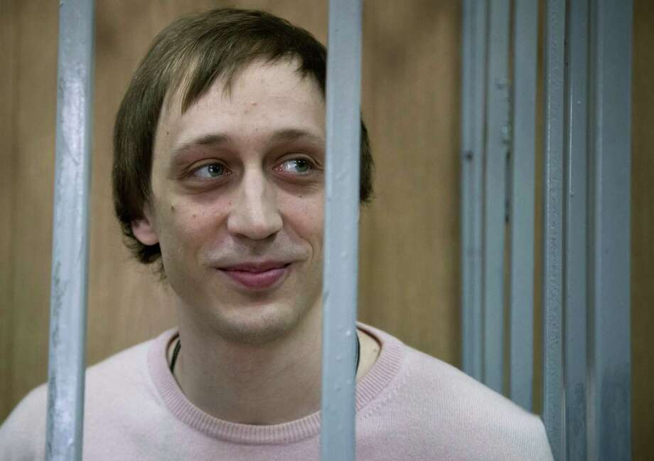 Pavel Dmitrichenko stands inside a barred enclosure at a courtroom in Moscow, Russia, Tuesday, Dec. 3, 2013. A judge found Dmitrichenko, a Bolshoi dancer and two other men guilty of an acid attack on the ballet's director.  The judge on Tuesday pronounced Bolshoi soloist Dmitrichenko guilty in the Jan. 17 attack on Sergei Filin. Photo: Alexander Zemlianichenko, AP / AP