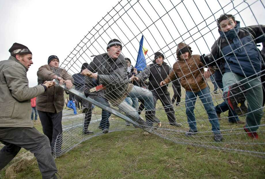 Anti-shale gas exploration protesters bring down a fence in Pungesti, north eastern Romania, Saturday, Dec. 7, 2013. Hundreds of villagers destroyed the fences around a plot of land owned by US energy company Chevron, during protests meant to stop shale gas exploration in the area. Photo: Mircea Restea, AP / AP