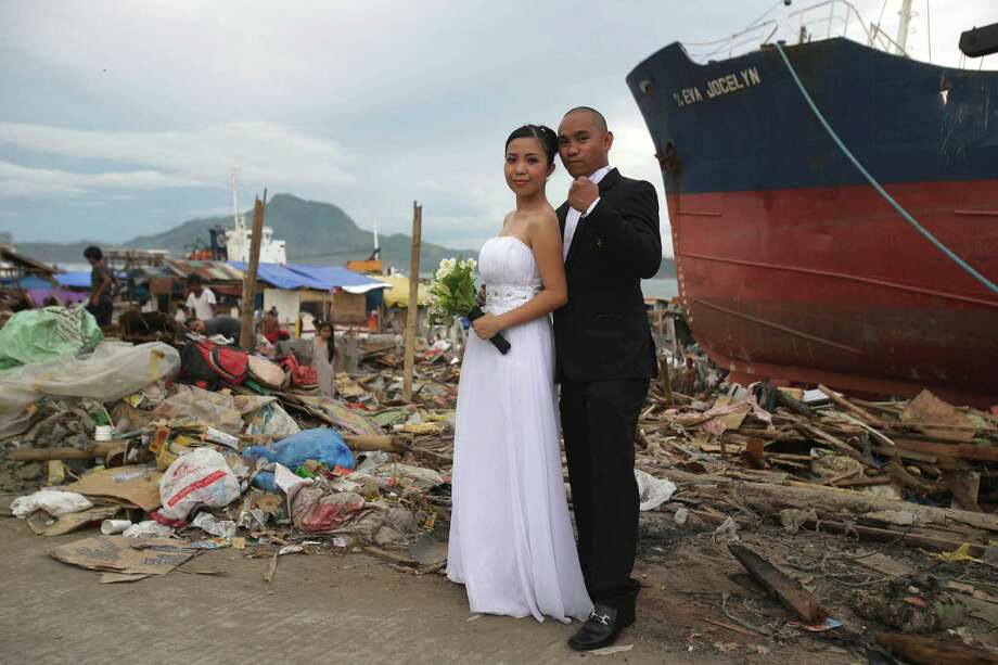 In this photo taken on Saturday, Dec. 7, 2013, Filipino groom Earvin Nierva, left, pumps his fist beside his bride Riza as they pose for their wedding pictures in the typhoon-ravaged city of  Tacloban, central Philippines. One month since Typhoon Haiyan, signs of progress in this shattered Philippine city are mixed with reminders of the scale of the disaster and the challenges ahead: Bodies are still being uncovered from beneath the debris. Tens of thousands are living amid the ruins of their former lives, underneath shelters made from scavenged materials and handouts. Photo: Aaron Favila, AP / AP