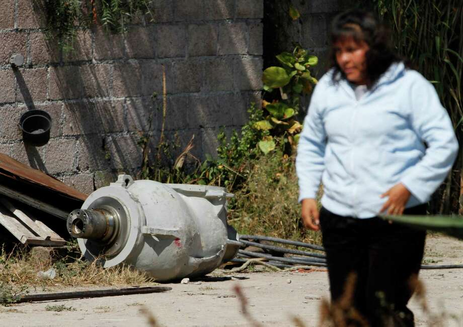 A woman walks near a radiation head that was part of a radiation therapy machine, in the patio of the family who found the abandoned radiation head in a nearby field in the village of Hueypoxtla, Mexico, Thursday, Dec. 5, 2013.  Officials were engaged Thursday in the delicate task of recovering the stolen shipment of highly radioactive cobalt-60 abandoned in a rural field in central Mexico state. According to National Commission of Nuclear Safety and Safeguards, the radioactive source had been removed from the radiation head and was found nearby in an empty lot. Photo: Marco Ugarte, AP / AP2013