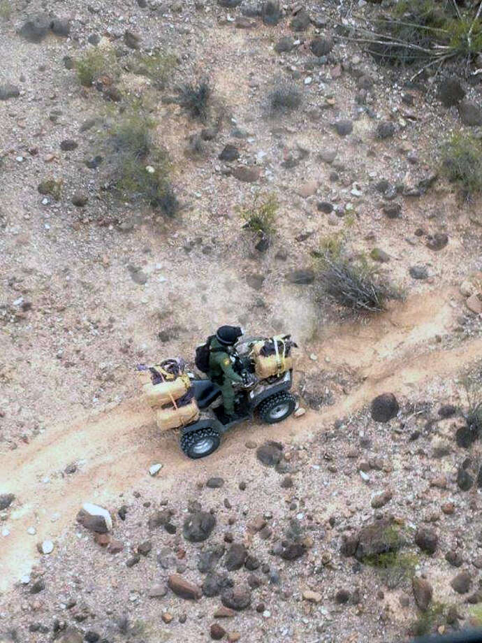 This Dec. 4, 2013 photo provided by Customs and Border Protection shows an agent transporting marijuana bundles found during an operation in the desert on the Tohono Odham Nation, Ariz. Tucson Sector Border Patrol agents arrested eight smugglers, six illegal immigrants, and seized four all-terrain vehicles, and 5,000 pounds of marijuana during the investigation. Photo: AP / Customs and Border Protection