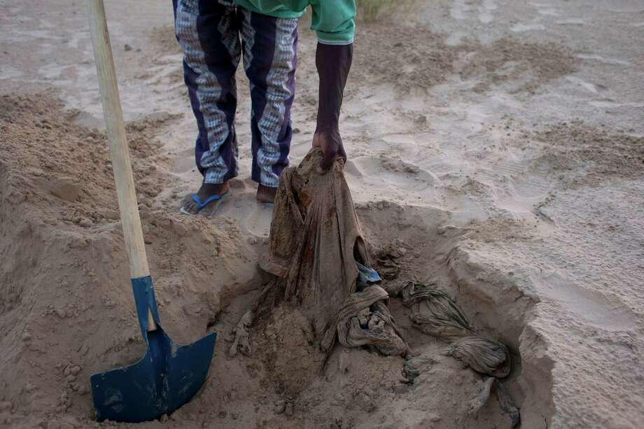 "In this July 23, 2013 photo, Sidi Fassoukoy, searching for his missing brother, unearths the remains of two men buried in the desert outside Timbuktu, Mali. From the men's clothing, Fassoukoy was able to identify the bodies as those of his brother, Maouloud Fassoukoy, and their neighbor, ""Vieux"" Ali Ould Kabbad, a lifelong Arab resident of Timbuktu whom Maouloud was killed for defending. Mali's military has killed or taken away at least 35 civilians in 2013, many of them Arabs and Tuaregs, according to human rights groups. An AP investigation uncovered the remains of six of these men, whose families identified the bodies and said they were last seen being taken away by Malian soldiers. Photo: Rebecca Blackwell, AP / AP"