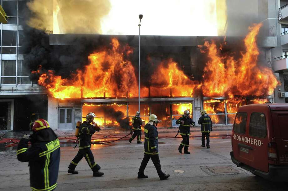 Firefighters attempt to extinguish a fire in a burning warehouse of Chinese products, in the northern Greek port city of Thessaloniki, Wednesday, Dec. 4, 2013. The fire lasted over three hours destroying the warehouse and goods. Photo: Nikolas Giakoumidis, AP / NIKOLAS GIAKOUMIDIS2013