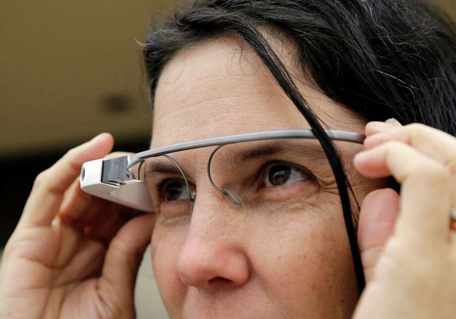 Cecilia Abadie models her Google Glass as she talks with her attorney outside of traffic court Tuesday, Dec. 3, 2013, in San Diego. When Abadie was pulled over on suspicion of speeding in October, the officer saw she was wearing Google Glass and tacked on a citation usually given to drivers who may be distracted by a video or TV screen. She pleaded not guilty to both charges on Tuesday. Photo: Lenny Ignelzi, AP / AP2013