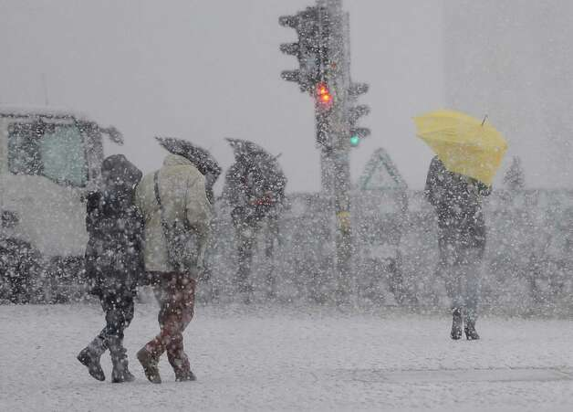 Pedestrians make their way during heavy snowfalls  near Berlin's central station Friday Dec. 6, 2013.  Weather forecasts predict ongoing stormy weather with low temperatures in Germany. Photo: Britta Pedersen, AP / AP2013