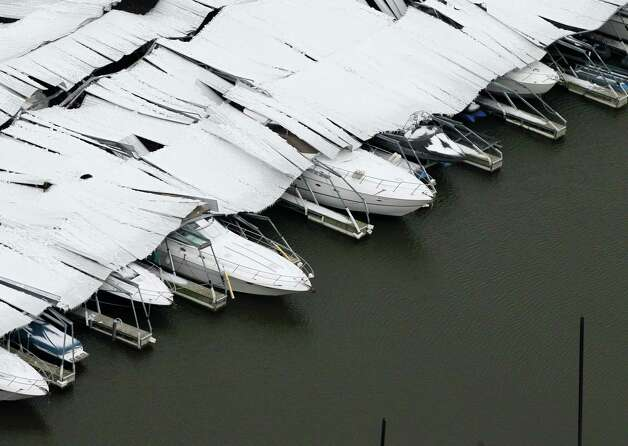 A section of a canopy that collapsed due to ice sits on several boats at Lake Lewisville, Saturday, Dec. 7, 2013, in Lewisville, Texas. Icy, treacherous sections of Interstate 35 north of Dallas were closed for hours at a time over the last day as tractor-trailers had trouble climbing hills, wrecks occurred and vehicles stalled, authorities said. Photo: Tony Gutierrez, AP / AP2013