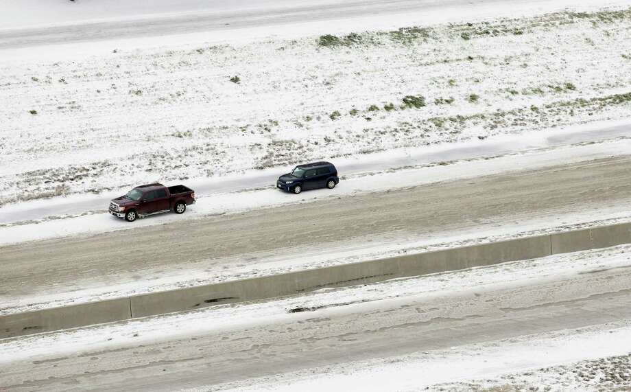 A vehicles sit abandoned on IH-35E south bound near, Saturday, Dec. 7, 2013, near Denton, Texas. Tractor trailer trucks sit at a complete stop on IH-35E south bound, Saturday, Dec. 7, 2013, near Denton, Texas. Icy, sections of Interstate 35 north of Dallas were closed for hours at a time over the last day as tractor-trailers had trouble climbing hills, wrecks occurred and vehicles stalled, authorities said. Photo: Tony Gutierrez, AP / AP