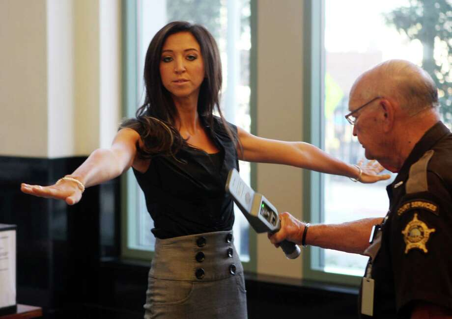 In a July 30, 2012 photo, Sarah Jones, former Dixie Heights High School teacher and Cincinnati Ben-Gal cheerleader, goes through security after arriving at the Kenton County Justice Center, in Covington, Ky.  From Twitter and Facebook to Amazon and Google, the biggest names of the Internet are blasting a federal judge�s decision in a defamation lawsuit by Jones, convicted of having sex with her former high school student.  The Internet giants recently filed briefs in the 6th U.S. Circuit Court of Appeals in Cincinnati.  The briefs are part of a lawsuit involving Jones against an Arizona-based website thedirty.com.  A jury found in July that posts on the site about Jones were substantially false and awarded her $338,000.  (AP Photo/The Enquirer, Patrick Reddy)  Photo: Patrick Reddy, AP / The Enquirer