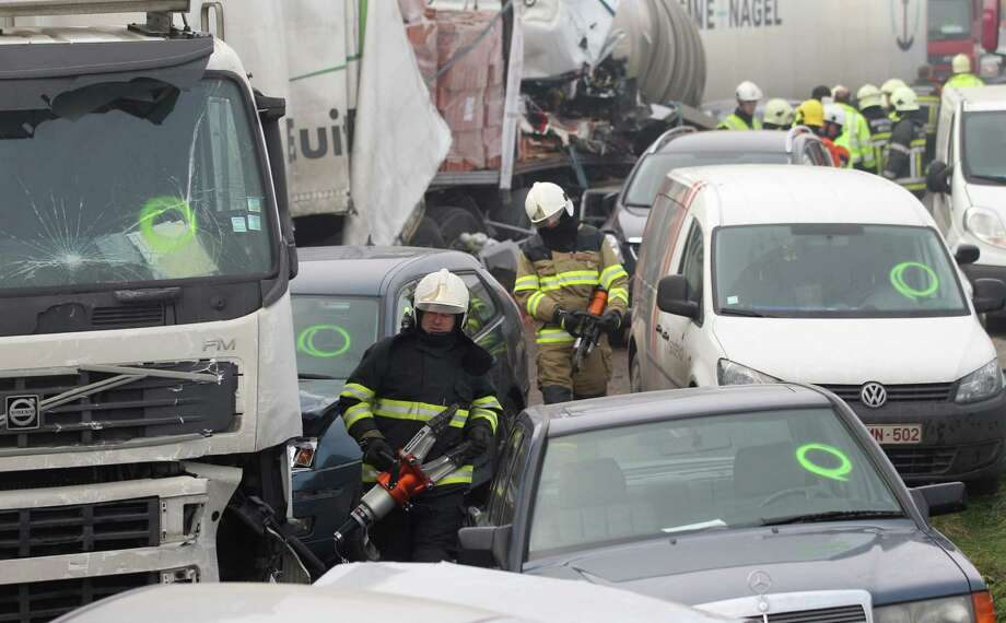 Firefighters carry heavy equipment at the scene of a crash on the A19 highway in Zonnebeke, western Belgium, Tuesday, Dec. 3, 2013.  Dozens of cars and trucks crashed in dense morning fog, and according to reports at least one person died in the crash and some dozens more were injured. Photo: Yves Logghe, AP / AP2012