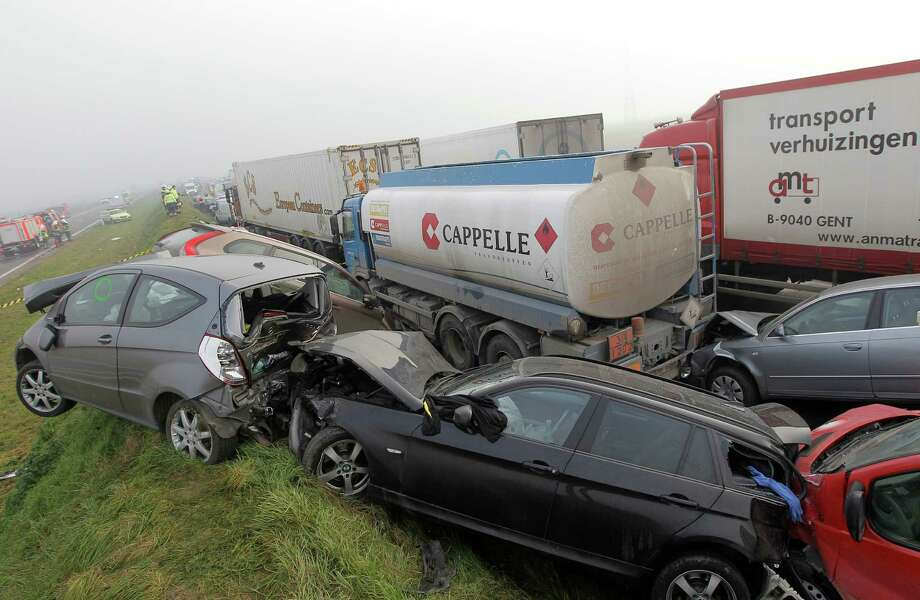 Crashed cars sit on top of a shoulder on the A19 highway in Zonnebeke, western Belgium, Tuesday, Dec.3, 2013.  Dozens of cars and trucks crashed in dense morning fog, killing at least one and injuring dozens more. Photo: Yves Logghe, AP / AP2012