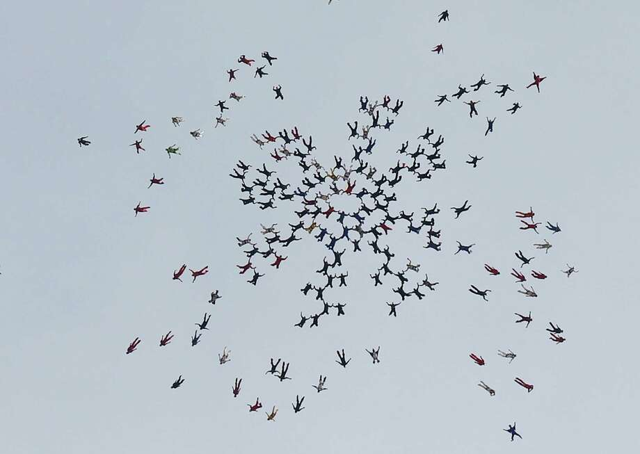 Skydivers, from all over the world, perform a group jump, the day after two skydivers were killed after colliding in midair during a jump from Skydive Arizona at Eloy Municipal Airport, on Wednesday, Dec. 4, 2013, in Eloy, Ariz. Participants said it was the best way to pay tribute to their friends in the tight-knit skydiving community who died. Photo: Ross D. Franklin, AP / AP2013