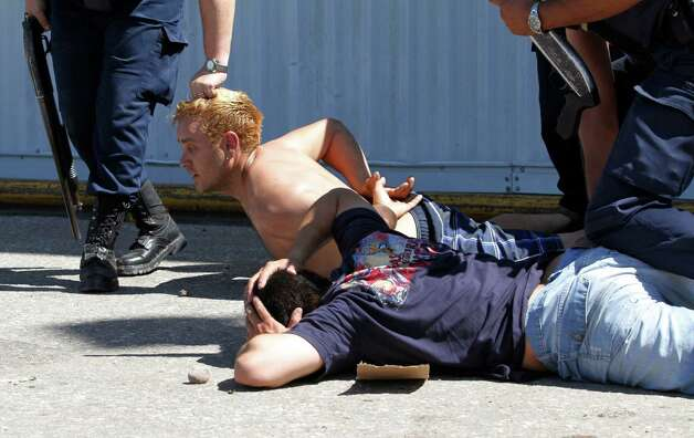 A police officer grabs a man by his hair as he and another man are detained by police outside a supermarket that was being looted in Cordoba, Argentina