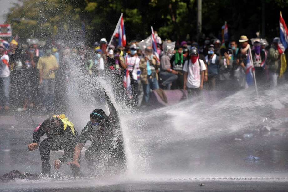 Anti-government protesters are sprayed water cannon by police in Bangkok, Thailand, Monday, Dec 2, 2013. Suthep Thaugsuban, the leader of Thailand's anti-government protests, said he met with Yingluck late Sunday in the presence of top military officials even though he has an arrest warrant against him. He later told cheering supporters that he told Yingluck that the only way to end the protests was for her to step down. He said his goal is to topple Yingluck by Wednesday. Photo: Vincent Thian, AP / AP2013