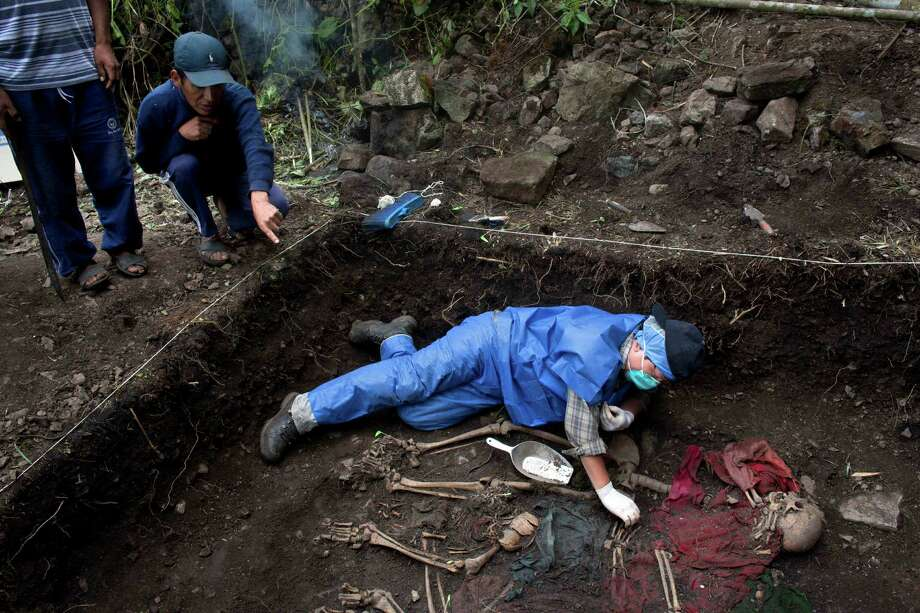 In this Nov. 13, 2013 photo, villager Julio Orihuela, 37, points to the mass grave in the village of Huallhua where his mother and sister were buried as forensic anthropologist Joel Tejada unearths their skeletal remains. The exhumation in the district of Chungui, Peru, bringing back traumatic memories for survivors of 1986-87, when soldiers and their paramilitary allies dismembered and killed women and children left behind by fleeing Shining Path rebels. Photo: Rodrigo Abd, AP / AP2013