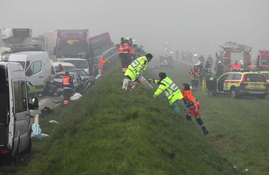 Medics carry equipment to a crash scene on the A19 highway in Zonnebeke, western Belgium, Tuesday, Dec.3, 2013.  Dozens of cars and trucks crashed in dense morning fog, killing at least one and injuring dozens more. Photo: Yves Logghe, AP / AP2012