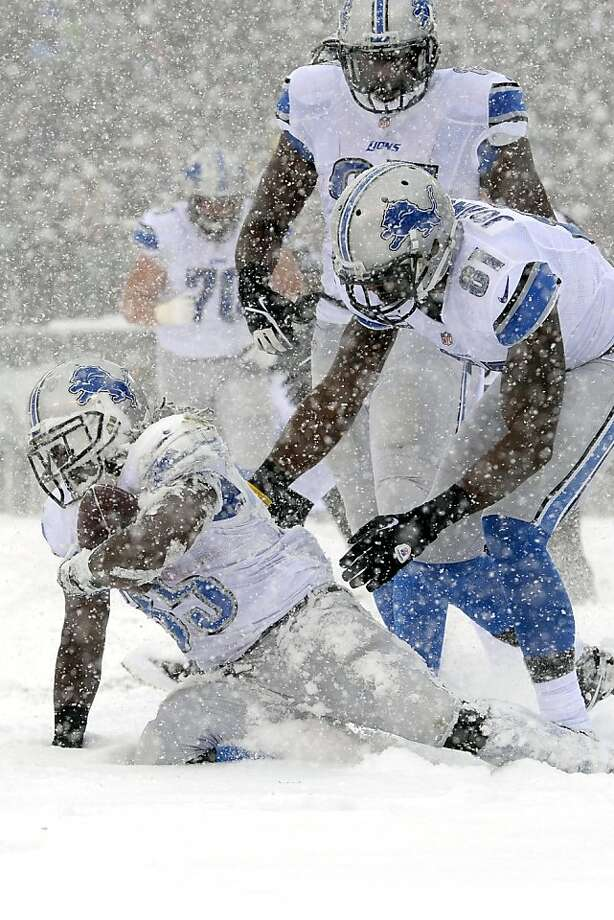 Detroit Lions' Joique Bell, left, gets up with the help of Brandon Pettigrew, center, and Calvin Johnson after scoring a touchdown during the first half of an NFL football game against the Philadelphia Eagles, Sunday, Dec. 8, 2013, in Philadelphia.  Photo: Michael Perez, Associated Press