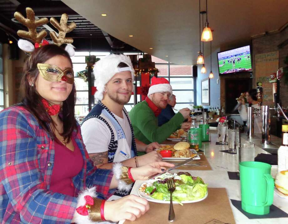 Paige Sadyan, Steve Ford and Dan Murphy enjoy a meal Saturday at Mama's Boy Southern Table and Refuge, one of seven stops on the first-ever SoNo Santa Crawl. Photo: Meg Barone / Norwalk Citizen contributed