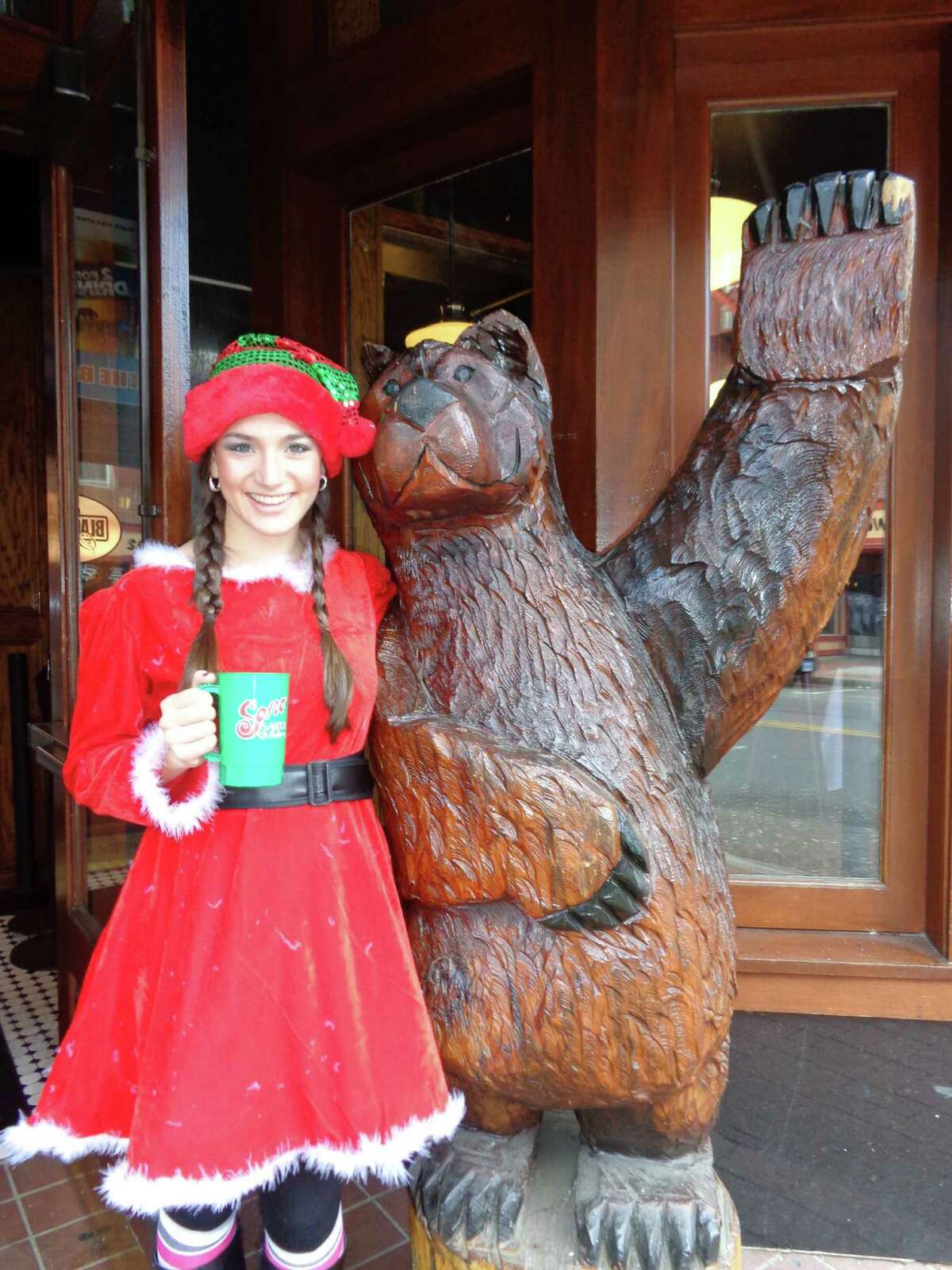 Kimberly Woodruff, a student at Sacred Heart University, poses with the carved wood bear statue in front of the Black Bear Saloon in SoNo as she arrives for the first-ever Santa Crawl on Saturday.