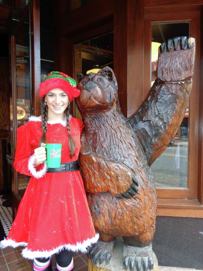 Kimberly Woodruff, a student at Sacred Heart University, poses with the carved wood bear statue in front of the Black Bear Saloon in SoNo as she arrives for the first-ever Santa Crawl on Saturday. Photo: Meg Barone / Norwalk Citizen contributed