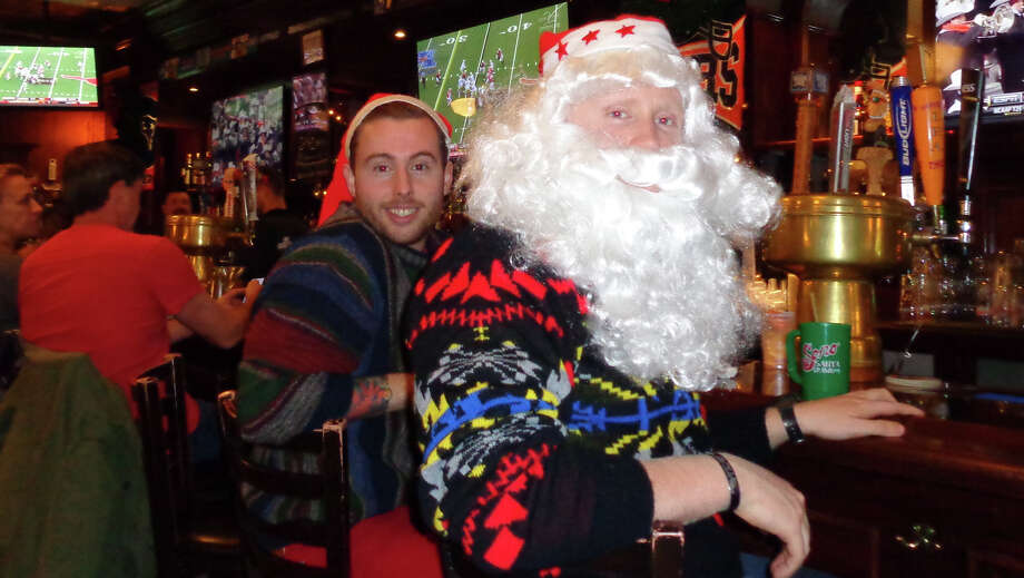 """Drew Allan of New Canaan, wearing a Santa cap, and a friend from Stamford who would only identify himself as """"Jeb,"""" were the first to arrive for the SoNo Santa Crawl at the Black Bear Saloon on Saturday. Photo: Meg Barone / Norwalk Citizen contributed"""