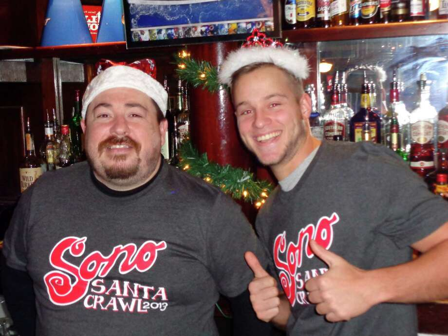 Albert Rodrigues, left, a bartender and manager at Black Bear Saloon, and Thomas Donahue, bar back, donned festive headgear to celebrate Saturday's SoNo Santa Crawl. Photo: Meg Barone / Norwalk Citizen contributed