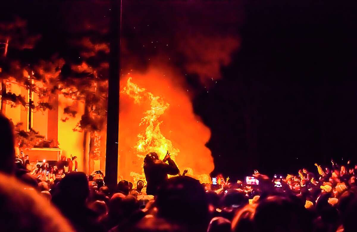 Revelers watch as a couch burns at Cedar Village in East Lansing, Mich., early Sunday, Dec. 8, 2013, as Michigan State University fans celebrate their team's win over Ohio State in the Big Ten Championship game. East Lansing police say they arrested