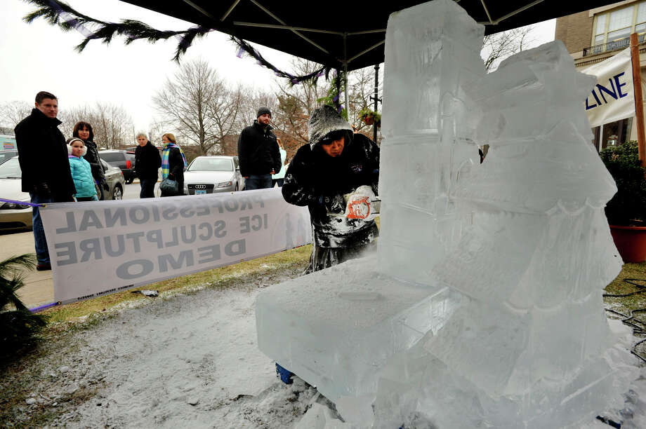 Christian Lopez, with Apple Ice / Ice Sculpture Designs, carves a sculpture with an electric chainsaw as onlookers watch during the annual Greenwich Holiday Stroll in downtown Greenwich, Conn., on Sunday, Dec. 8, 2013. Photo: Jason Rearick / Stamford Advocate