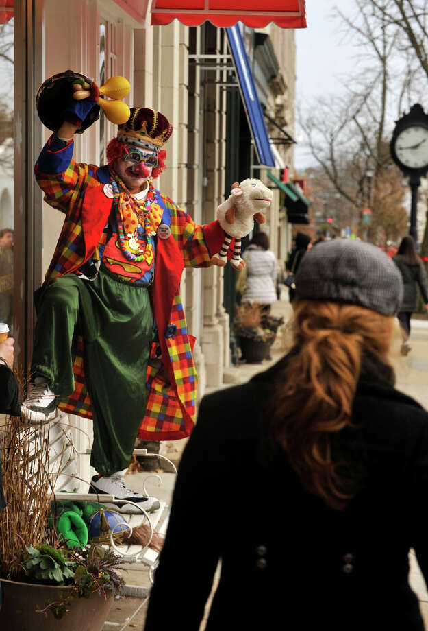 Dressed up as a clown, Freddy Contante greets passers by in front of La Fenice Gelateria during the annual Greenwich Holiday Stroll in downtown Greenwich, Conn., on Sunday, Dec. 8, 2013. Photo: Jason Rearick / Stamford Advocate