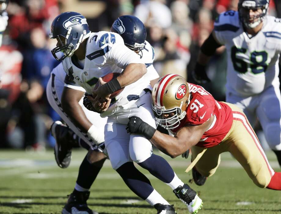 San Francisco 49ers' defensive end Ray McDonald, right, sacks Seattle Seahawks quarterback Russell Wilson (3) in the first half of an NFL football game on Sunday, Dec. 8, 2013, in San Francisco. (AP Photo/Marcio Jose Sanchez) Photo: Marcio Jose Sanchez, AP