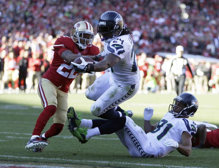 Seattle Seahawks running back Marshawn Lynch (24) rushes for a touchdown as San Francisco 49ers cornerback Carlos Rogers, left, looks on in the first half of an NFL football game, Sunday, Dec. 8, 2013, in San Francisco. At right is Seattle Seahawks wide receiver Golden Tate. (AP Photo/Ben Margot) Photo: Ben Margot, AP