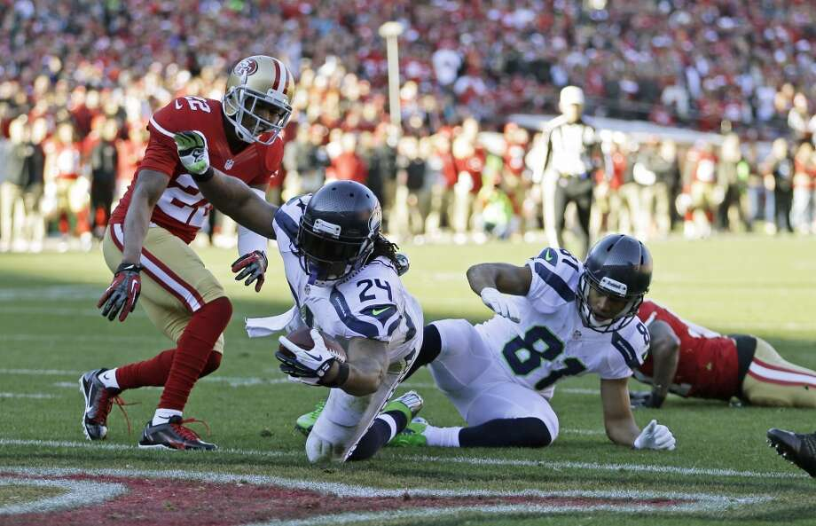Seattle Seahawks running back Marshawn Lynch (24) dives into the end zone for a touchdown as San Francisco 49ers cornerback Carlos Rogers, left, looks on, in the first half of an NFL football game, Sunday, Dec. 8, 2013, in San Francisco. At right is Seattle Seahawks wide receiver Golden Tate (81). (AP Photo/Ben Margot) Photo: Ben Margot, AP