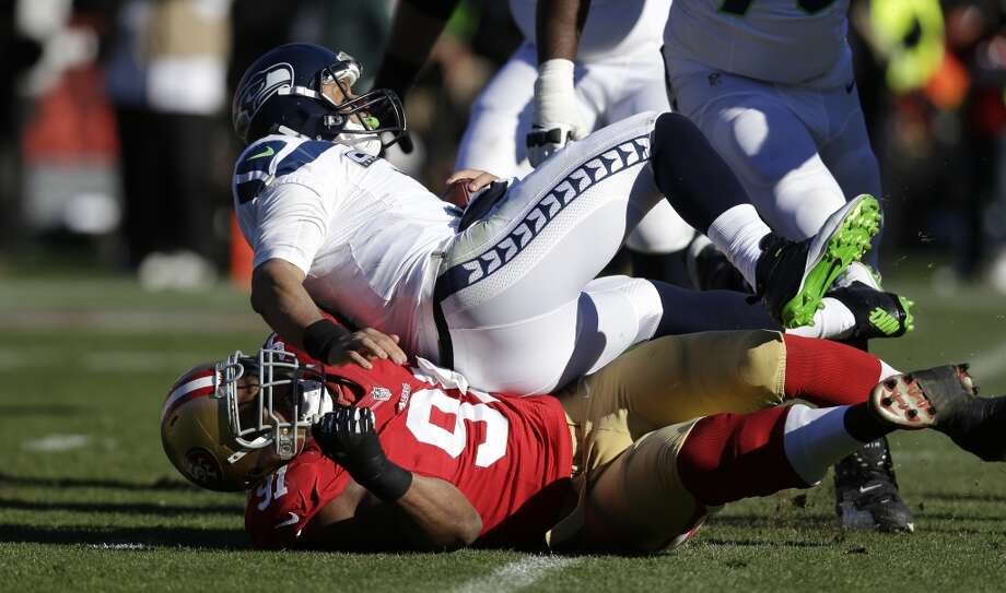 San Francisco 49ers' defensive end Ray McDonald, bottom, sacks Seattle Seahawks quarterback Russell Wilson, top, in the first half of an NFL football game, Sunday, Dec. 8, 2013, in San Francisco. (AP Photo/Marcio Jose Sanchez) Photo: AP
