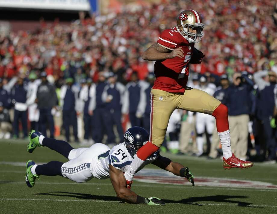 San Francisco 49ers quarterback Colin Kaepernick, right, runs with the ball before being brought down by Seattle Seahawks middle linebacker Bobby Wagner, left, in the first half of an NFL football game, Sunday, Dec. 8, 2013, in San Francisco. (AP Photo/Ben Margot) Photo: AP