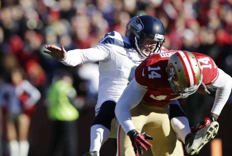 San Francisco 49ers' Kassim Osgood, left, collides with Seattle Seahawks kicker Jon Ryan, right, after Osgood blocked Ryan's punt in the first half of an NFL football game, Sunday, Dec. 8, 2013, in San Francisco. (AP Photo/Marcio Jose Sanchez) Photo: AP