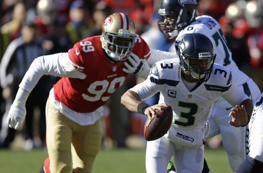 Seattle Seahawks quarterback Russell Wilson, right, runs with the ball as San Francisco 49ers outside linebacker Aldon Smith, left, looks on in the first half of an NFL football game, Sunday, Dec. 8, 2013, in San Francisco. In the background is Seattle Seahawks tackle Russell Okung (76). (AP Photo/Ben Margot) Photo: AP