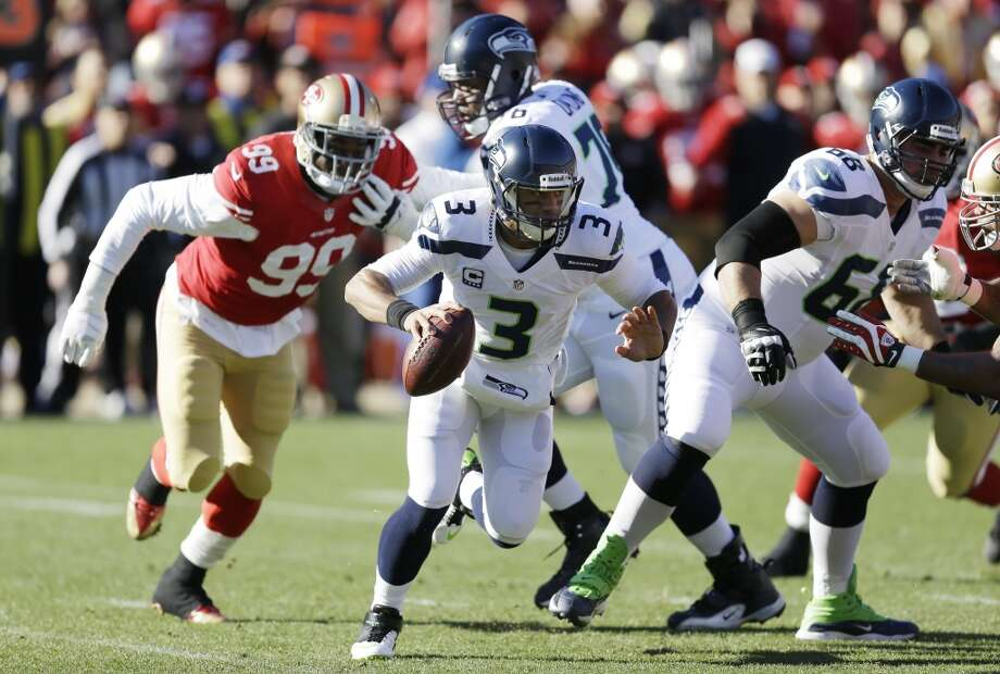 Seattle Seahawks quarterback Russell Wilson (3) scrambles as San Francisco 49ers outside linebacker Aldon Smith (99) pursues him in the first half of an NFL football game, Sunday, Dec. 8, 2013, in San Francisco. (AP Photo/Ben Margot) Photo: AP
