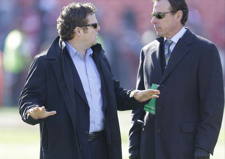 Seattle Seahawks general manager John Schneider, left, talks with Seahawks President Peter McLoughlin, right, on the field before an NFL football game against the San Francisco 49ers, Sunday, Dec. 8, 2013, in San Francisco. (AP Photo/Ben Margot) Photo: AP