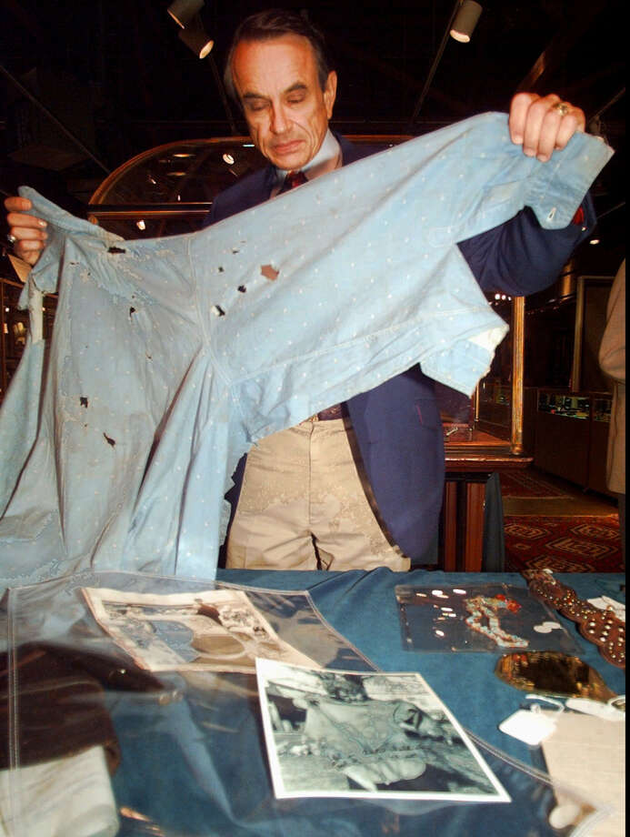 Greg Martin, director of the Arms & Armor Dept. at Butterfields auction house, holds up the bullet-riddled death shirt of Clyde Barrow. It was auctioned for $75,000 in San Francisco in 1997. Photo: Associated Press