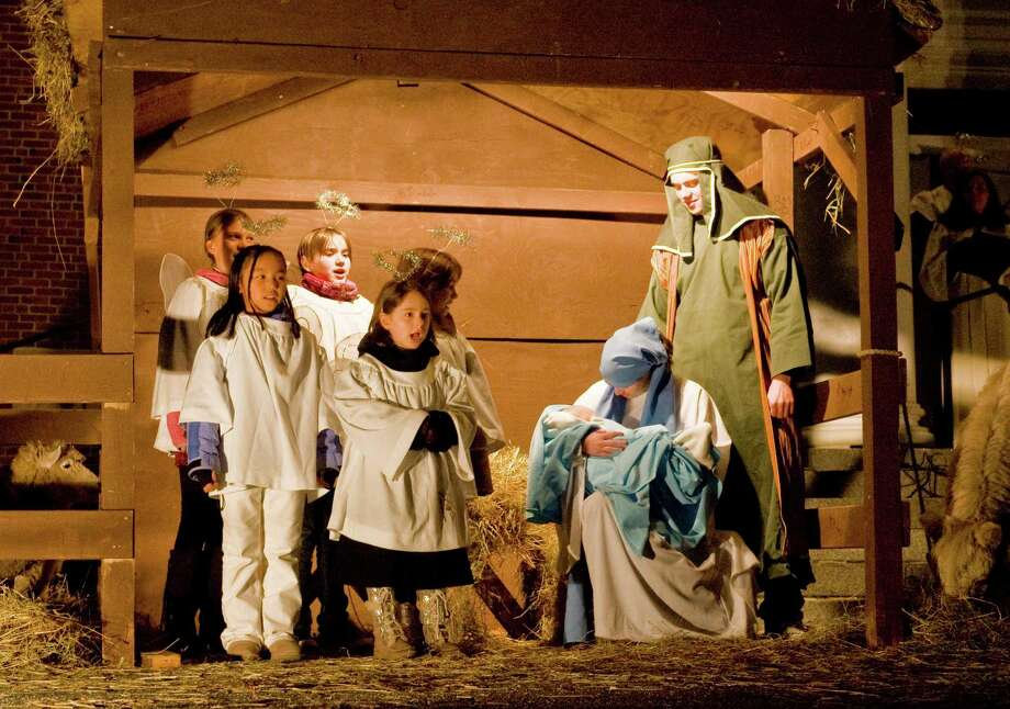 Little angels sing as the baby Jesus, played by six month old Elijah Condon of Newtown, is held by Mary, played by Katarina von Kuhn, as Joseph, played by Nate Pfohl, both Ridgefield High School seniors, watches during the annual ìLiving Nativityî at Jesse Lee Memorial United Methodist Church in Ridgefield. Sunday, Dec. 8, 2013 Photo: Scott Mullin / The News-Times Freelance