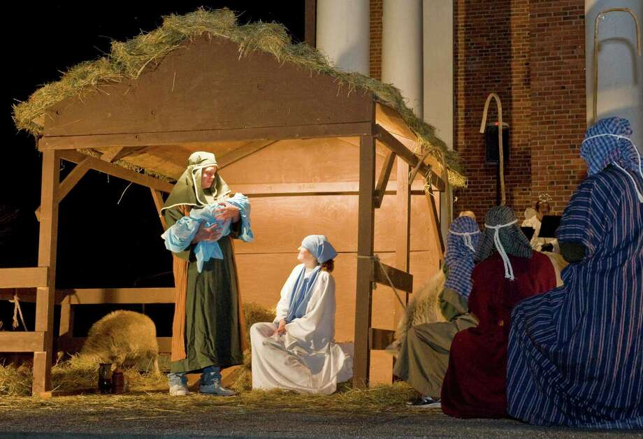 Joseph, played by Nate Pfohl, a Ridgefield High School senior, holds the baby Jesus, played by six month old Elijah Condon of Newtown as Mary, played by Katarina von Kuhn, also a Ridgefield High School senior, sits and watches during the annual ìLiving Nativityî at Jesse Lee Memorial United Methodist Church in Ridgefield. Sunday, Dec. 8, 2013 Photo: Scott Mullin / The News-Times Freelance
